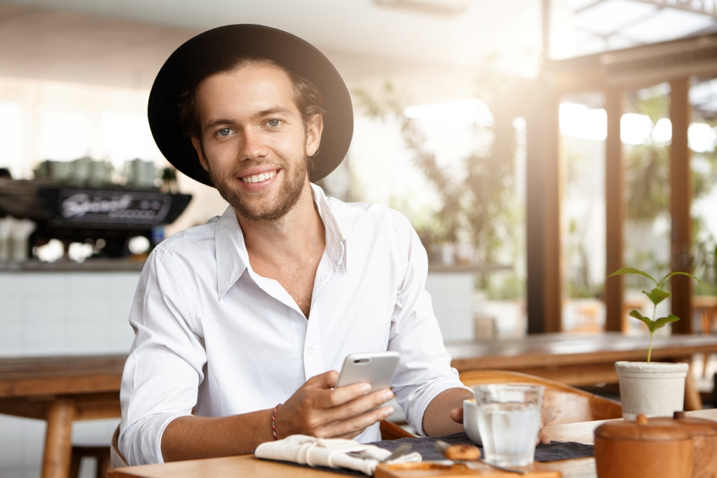 Attractive happy young bearded businessman in trendy hat texting messages via social networks and browsing internet, using free wifi on his electronic device during coffee break at restaurant